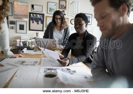 Photo editor production team reviewing photo proofs in office meeting - Stock Photo
