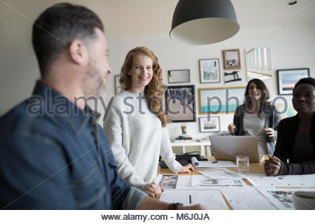 Smiling photo editor production team reviewing photo proofs in office meeting - Stock Photo
