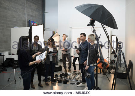 Photographers and production team meeting, preparing for photo shoot in studio - Stock Photo