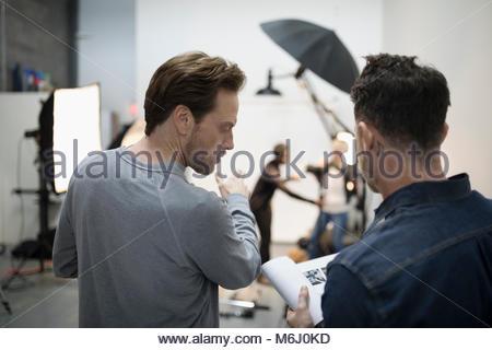 Photographer and production team preparing photo shoot in studio - Stock Photo