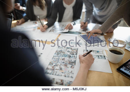 Production team editing photo proofs in office meeting - Stock Photo