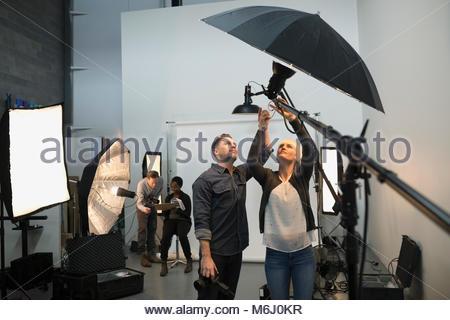 Photographers and production team preparing lighting equipment for photo shoot in studio - Stock Photo
