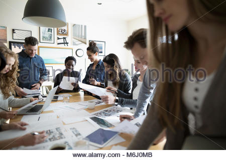 Production team reviewing photo proofs in office meeting - Stock Photo
