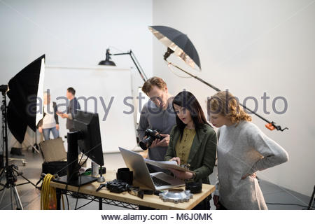 Photographer and production team preparing photo shoot in studio - Stock Photo