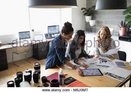 Female photo editors with digital tablet reviewing photo proofs in office - Stock Photo