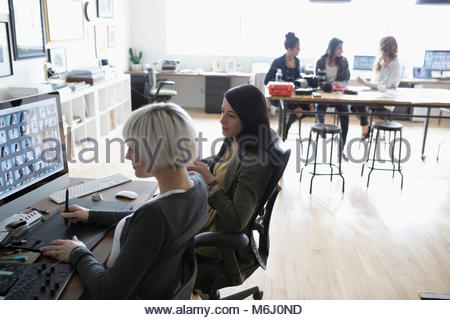 Female photo editors with graphics tablet editing digital photo proofs on computer in office - Stock Photo