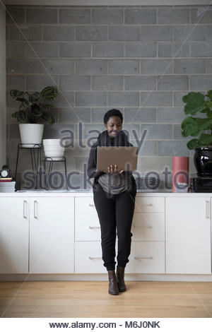 Smiling businesswoman using laptop, standing in office - Stock Photo