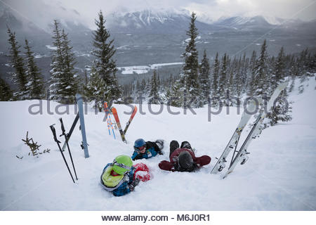 Family skiers relaxing, laying on snowy mountain - Stock Photo