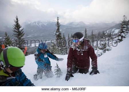 Playful family skiers enjoying snowball fight on snowy mountain - Stock Photo