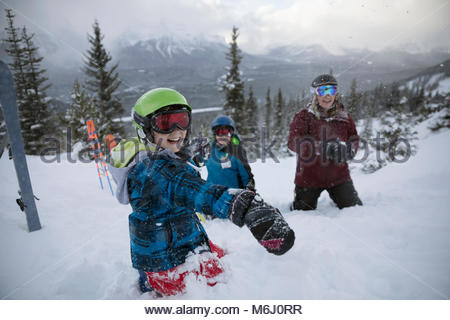 Portrait playful boy skier enjoying snowball fight with family on snowy mountain - Stock Photo