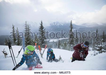 Family skiers enjoying snowball fight on snowy mountain - Stock Photo