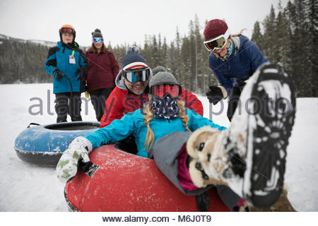 Portrait playful family inner tubing in snow at tube park - Stock Photo