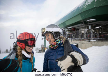 Happy mother and daughter skiers at ski resort - Stock Photo