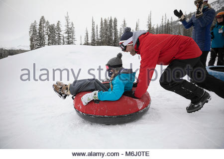 Father pushing daughter in inner tube in snow at tube park - Stock Photo