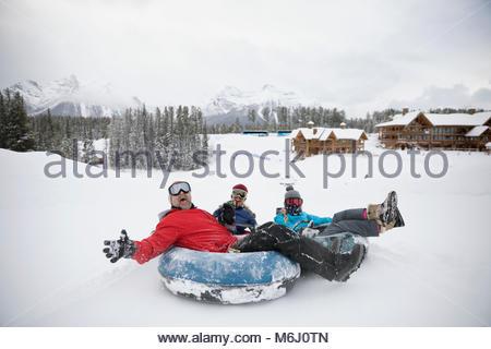 Portrait playful family inner tubing in snow at ski resort tube park - Stock Photo