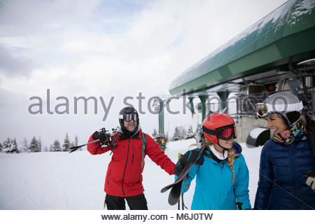 Family skiers carrying skis from ski resort gondola - Stock Photo