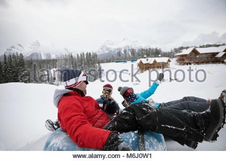Playful family inner tubing in snow at ski resort tube park - Stock Photo