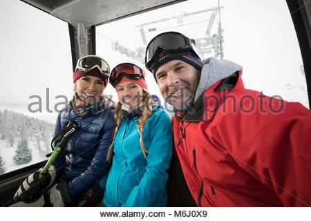 Portrait smiling family skiers taking selfie in gondola - Stock Photo