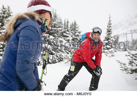 Playful couple snowshoeing, enjoying snowball fight in snow - Stock Photo