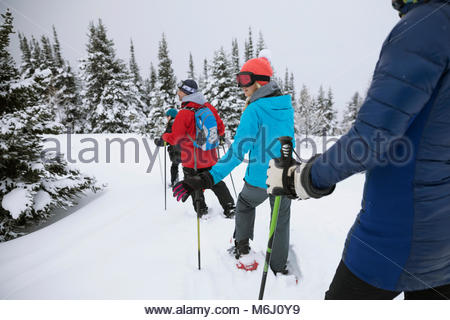 Family snowshoeing in snow - Stock Photo
