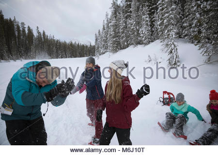Playful family snowshoeing, enjoying snowball fight - Stock Photo
