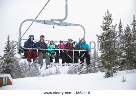 Portrait smiling family and friend skiers riding chair lift at ski resort - Stock Photo
