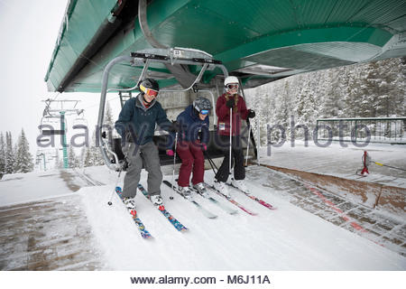 Family skiers getting off chair lift at ski resort - Stock Photo