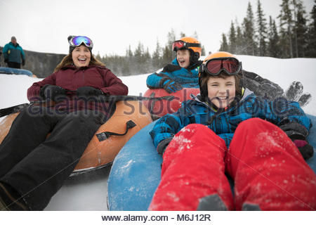 Happy mother and sons inner tubing in snow at tube park - Stock Photo