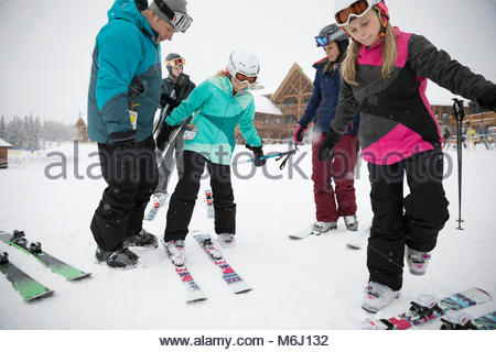 Family skiers preparing skis outside ski resort lodge - Stock Photo
