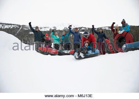 Portrait family cheering, inner tubing in snow at snow park - Stock Photo
