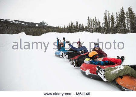 Playful family inner tubing in snow at tube park - Stock Photo