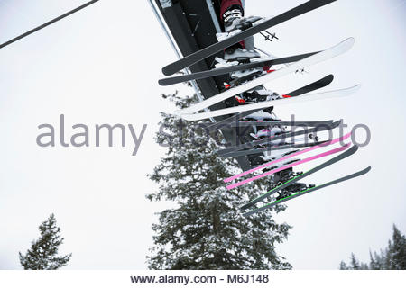 Skier skis dangling from chair lift - Stock Photo