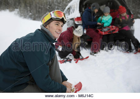 Smiling young man putting on snowshoes with family at car in snow - Stock Photo