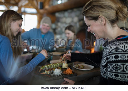 Smiling female skier eating sushi with family at ski resort lodge restaurant apres-ski - Stock Photo