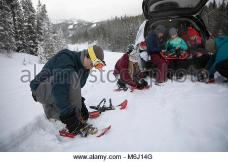 Family preparing for snowshoeing at car in remote snow - Stock Photo