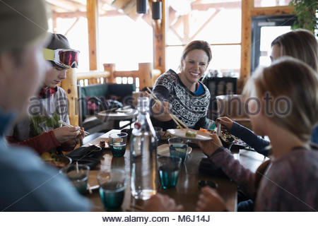Family skiers enjoying sushi at ski resort restaurant apres-ski - Stock Photo