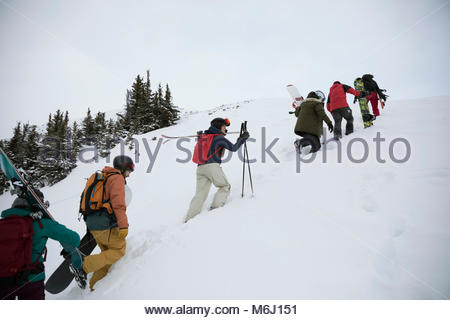 Skiers and snowboarders hiking snowy hill - Stock Photo