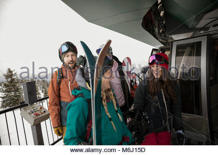 Skier and snowboarder friends getting in gondola at ski resort - Stock Photo