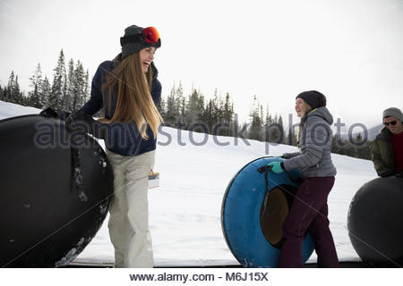 Friends carrying inner tubes in snow - Stock Photo