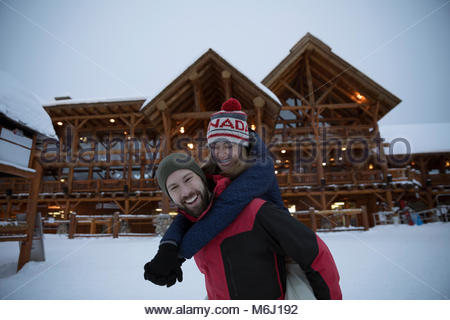 Playful, romantic skier couple playing in snow outside ski resort lodge - Stock Photo