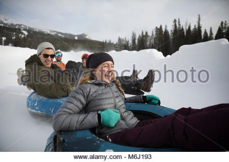 Playful, happy friends riding inner tubes in snow - Stock Photo