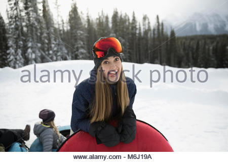 Portrait silly woman with inner tube making a face in snow - Stock Photo