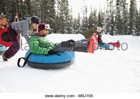 Friends racing, inner tubing in snow - Stock Photo
