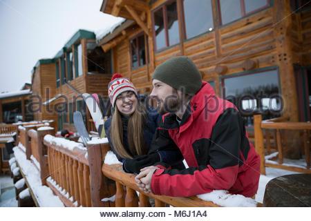 Skier couple talking on snowy ski resort lodge balcony - Stock Photo