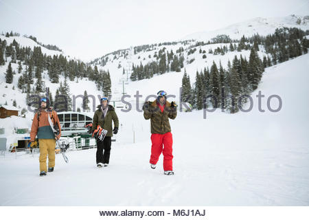 Male snowboarder friends carrying snowboards in ski resort snow - Stock Photo