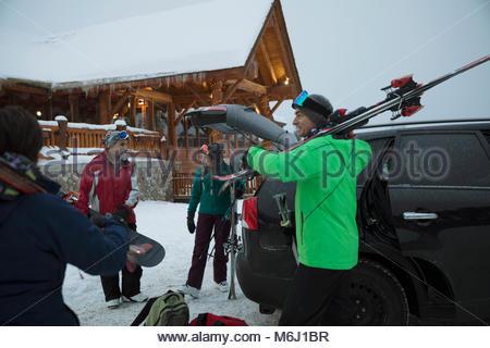Skier family unloading skis from car outside snowy ski resort lodge - Stock Photo
