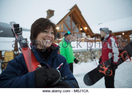 Happy mature woman carrying skis outside snowy ski resort lodge - Stock Photo