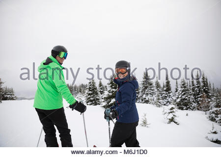 Portrait smiling couple skiing in snow - Stock Photo