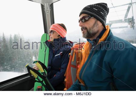 Mature couple skiers riding gondola - Stock Photo