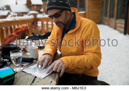 Male skier enjoying breakfast, preparing with map on snowy ski resort balcony - Stock Photo